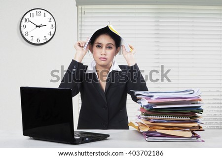 Picture of tired businesswoman working in the office with a pile of document and laptop, putting a paperwork on her head - stock photo