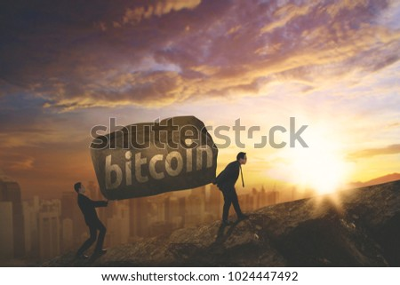 Picture of two businessmen carrying a stone with bitcoin word while climbing on the cliff