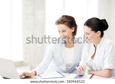 picture of two businesswomen working with laptop in office - stock photo