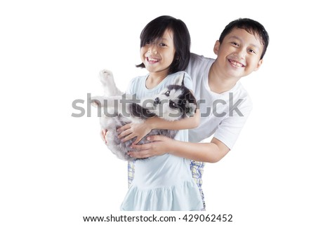 Picture of two cheerful children playing in the studio and smiling at the camera while holding a siberian husky puppy