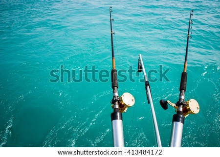 Picture of two commercial fishing poles over turquoise water with copy space - stock photo