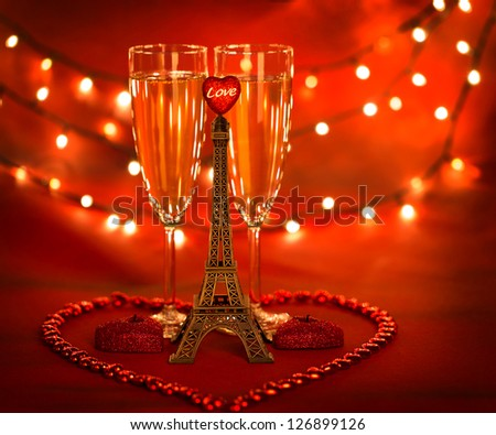 Picture of two glass with champagne decorated with little Eiffel tower and heart-shaped candles and beads on red background with glowing lights, honeymoon in Paris, romantic holiday, Valentines day - stock photo