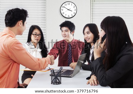 Picture of two male managers closing a business meeting by shaking hands in front of their employees, shot in the office - stock photo