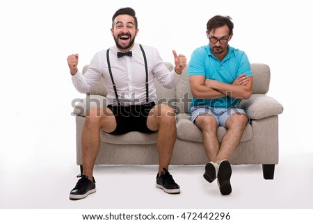 Picture of two men sitting on couch or sofa and looking at camera isolated on white background. Man in glasses looking sad or disappointed. Emotions concept.