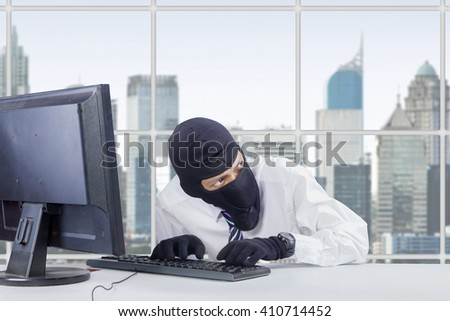 Picture of watchful thief wearing mask while stealing information on the computer in office - stock photo