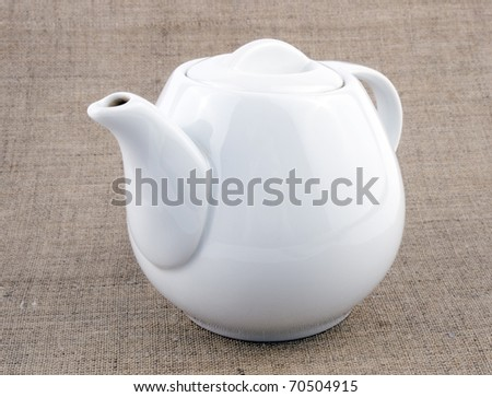 Picture of white teapot on linen background