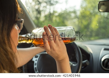 picture of woman drinking alcohol in the car. - stock photo