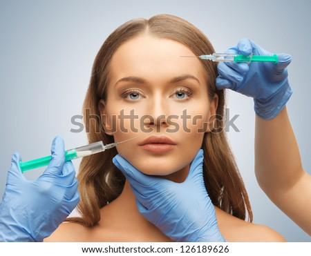 picture of woman face and beautician hands with syringes