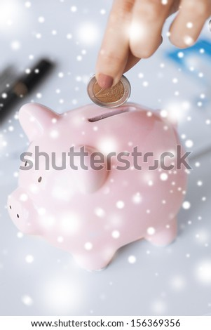 picture of woman hand putting coin into small piggy bank - stock photo