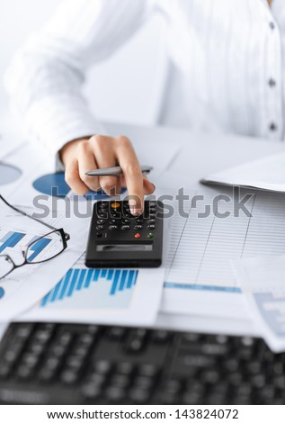 picture of woman hand with calculator and papers - stock photo