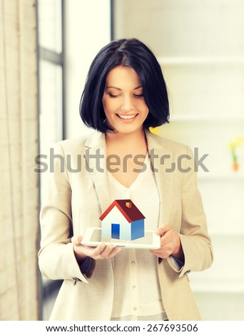 picture of woman holding tablet pc with house illustration - stock photo