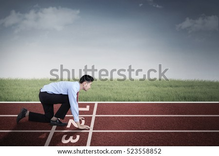 Picture of young Arabian businessman in ready position while kneeling in the line start on the track