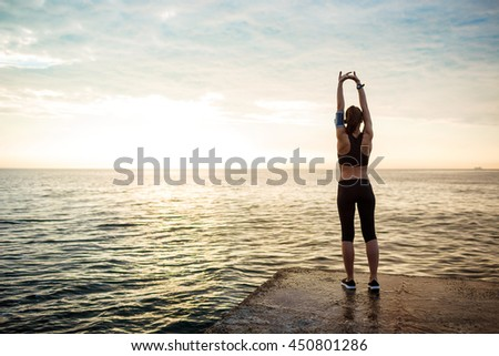 Picture of young beautiful fitness girl makes sport exercises with sea on background