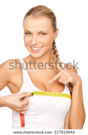 picture of young beautiful woman measuring her breast - stock photo