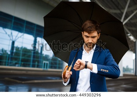 Picture of  young  businessman holding  umbrella and looking on watch in rainy terminal