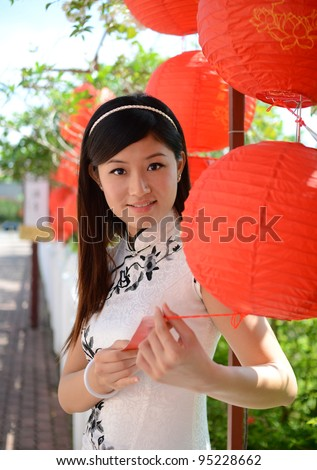Picture of young chinese woman wearing traditional cheongsam posing in outdoor - stock photo