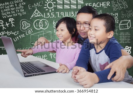 Picture of young male teacher teaching his students with laptop computer in the classroom - stock photo
