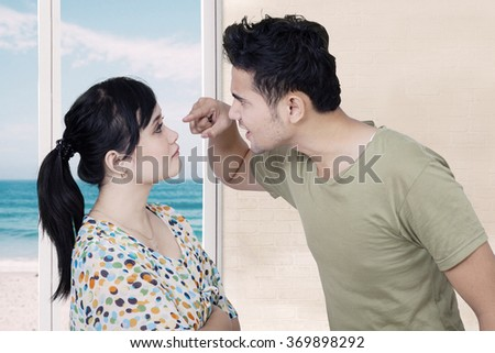 Picture of young man looks angry and scolding his wife while screaming and pointing at her face