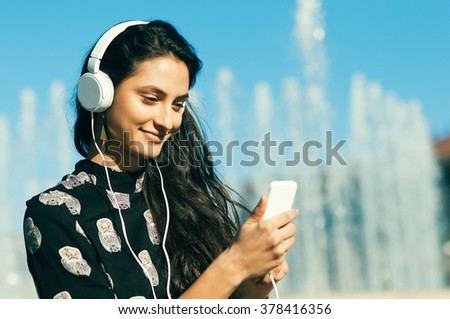 Picture of young smiling woman with earphones outside listening music on a sunny day - stock photo