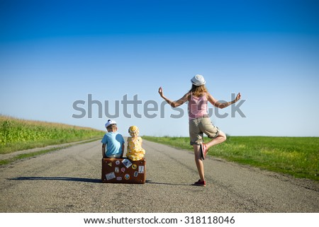 Picture of young woman meditating and two children sitting on old suitcase on country road. Backview of family traveling and waiting on blue sky sunny outdoors background. - stock photo