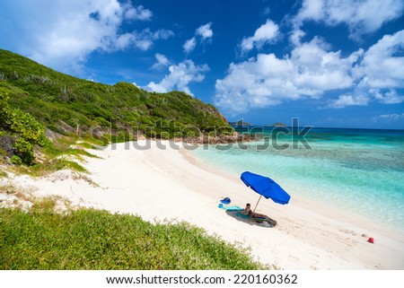 Picture perfect beach with blue umbrella, white sand, turquoise ocean water and blue sky at tropical island in Caribbean - stock photo