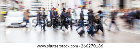 picture with camera made zoom effect of crossing people on a wet city street - stock photo