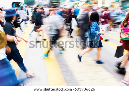 picture with motion blur of a crowd of people crossing a street in Hong kong