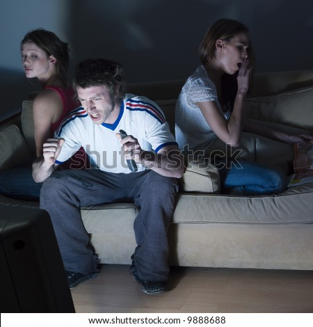 pictures in a living room of two young girls and a man sitting on a couch  watching on tv  sport event - stock photo