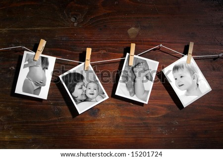 Pictures of a newborn and mother attach to rope with clothes spins on wooden background - stock photo