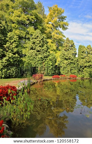 Picturesque bush with red flowers around a circular pond. Beautiful park in northern Italy Sigurta - stock photo
