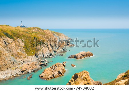 Picturesque cliffs, ocean and headland landscape and Dongju lighthouse on Juguang Island on the Matsu Islands of Taiwan.  Horizontal - stock photo