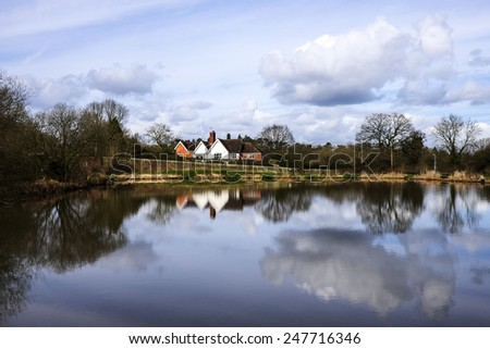 picturesque english cottage next to water - stock photo