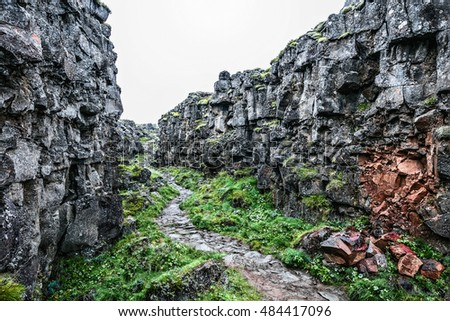 Picturesque hiking trail in rocky canyon with green grass in Iceland