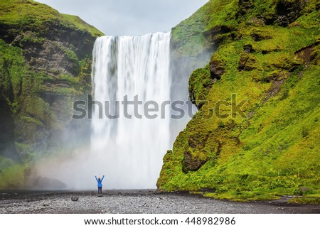 Picturesque huge rainbow appears in the water mist. Middle-aged woman - tourist shocked beauty waterfall. Interesting waterfall in Iceland - Skogafoss - stock photo