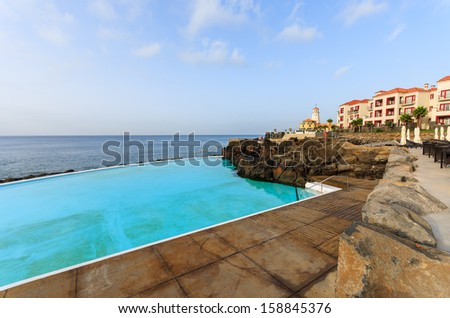 Picturesque infinity swimming pool at coast of Atlantic Ocean, Madeira island, Portugal  - stock photo