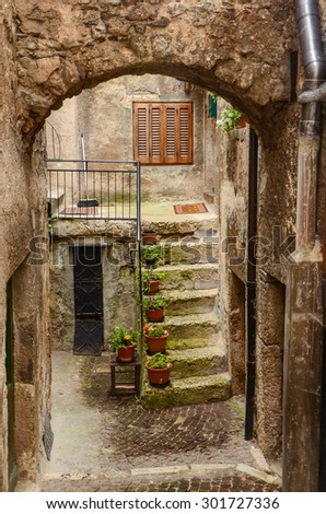 Picturesque Italian town Scanno - arch, courtyard, concrete staircase, flowers