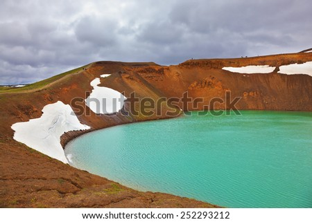 Picturesque Krafla lake in the crater of an extinct volcano. Lake water bright green color. On the shores lie snowfields from last year - stock photo