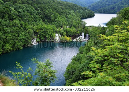 picturesque lake in forest high in mountains  with waterfalls  - stock photo
