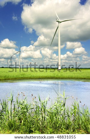 Picturesque landscape with wind generator  and lake on a background of the blue sky.  Picturesque landscape with wind generator  and lake on a background of the blue sky. - stock photo