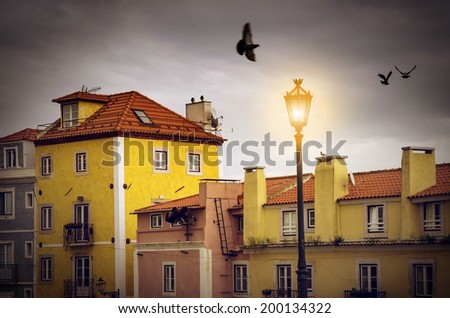 Picturesque Lisbon neighborhood with colorful block of houses under gray sky  - stock photo