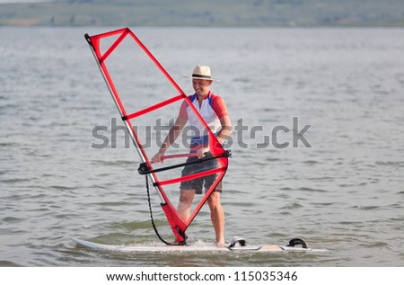 Picturesque man trying to balance with child's sail on windsurfing board