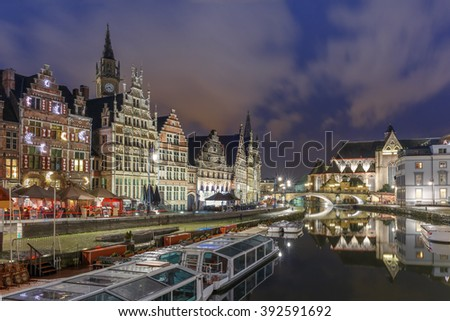 Picturesque medieval building and St Michael's Bridge on the quay Graslei in Leie river at Ghent town at night, Belgium - stock photo