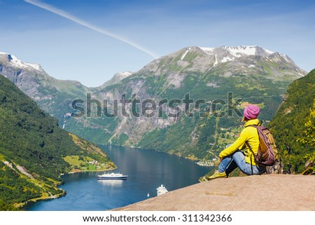 Picturesque Norway mountain landscape. Young girl enjoying the view near Geiranger fjord, Norway - stock photo