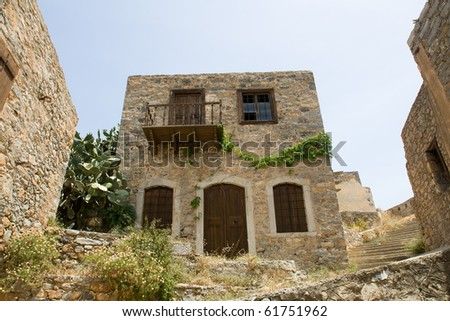 Picturesque old Mediterranean style abandoned lopsided rustic stone house with wooden sun blind, balcony in ancient town - stock photo