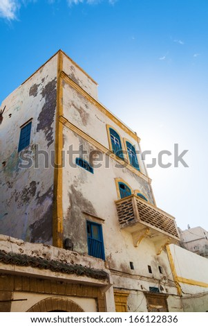 picturesque old white house with blue windows in Essaouira, Morocco