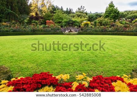 Picturesque Ornamental Park Garden Butchart Gardens On Vancouver Island,  Canada. Green Grass Lawn