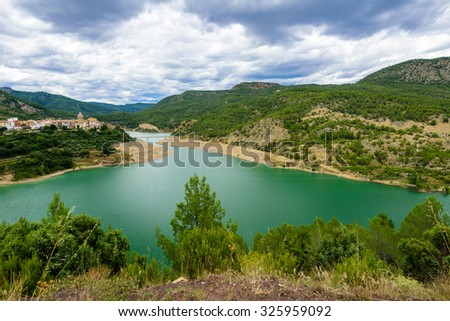 Picturesque panoramic landscape with Mijares river and Puebla de Arenoso town on the background, Alto Mijares, Castellon, Valencia, Spain. - stock photo
