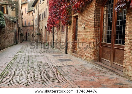 picturesque quiet brick alley in small town Certaldo Alto, Tuscany, Italy - stock photo
