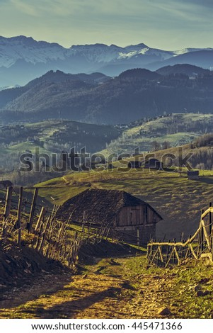 Picturesque spring rural scene with old Romanian wooden shack and country road uphill in Sirnea village, Brasov county, Romania. Travel destinations. - stock photo