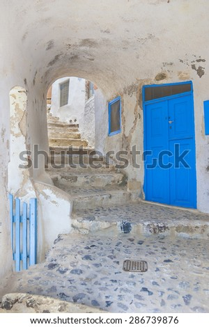 Picturesque stone arch near with traditional greek house in famous Oia village at summer sunny day.Santorini (Tira) island.Cyclades.Greece.Europe. - stock photo